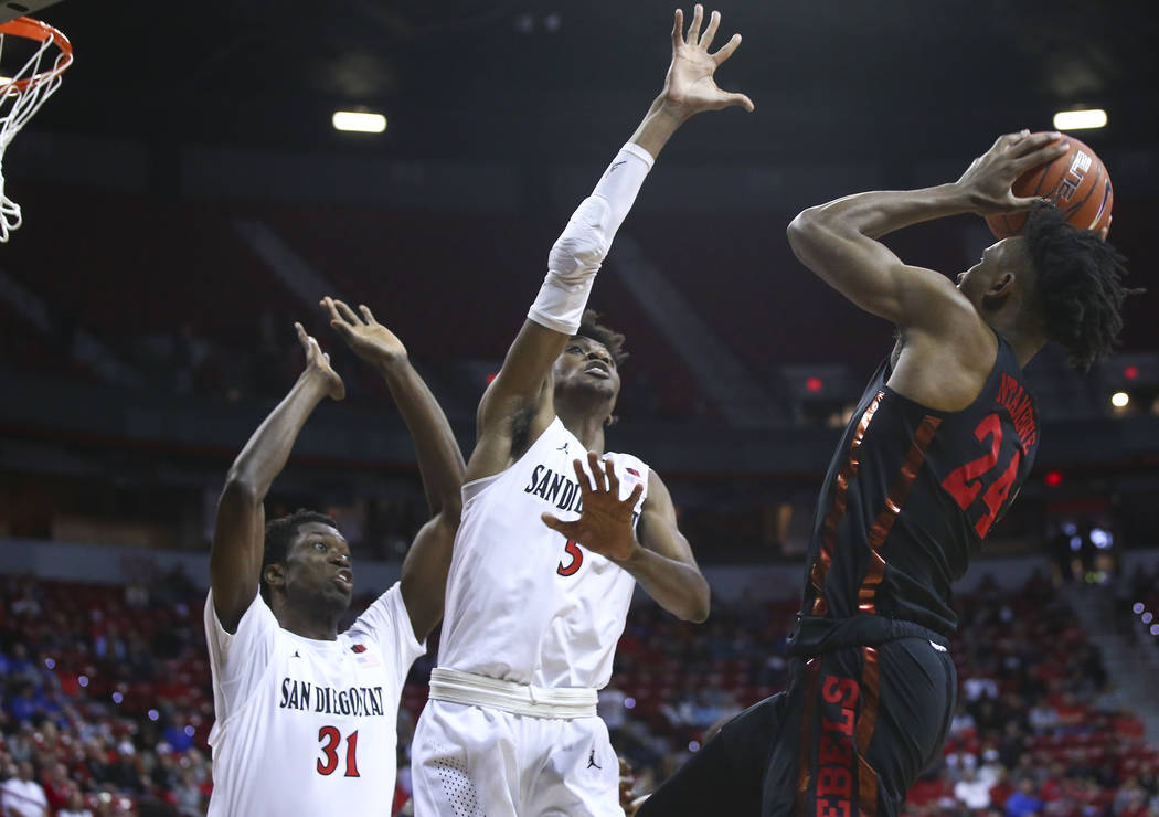 UNLV Rebels forward Joel Ntambwe (24) shoots against San Diego State Aztecs forwards Jalen McDaniels (5) and Nathan Mensah (31) during the first half of a quarterfinal game in the Mountain West me ...