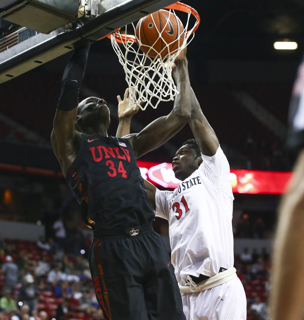 UNLV Rebels forward Cheikh Mbacke Diong (34) dunks against San Diego State Aztecs forward Nathan Mensah (31) during the first half of a quarterfinal game in the Mountain West men's basketball tour ...