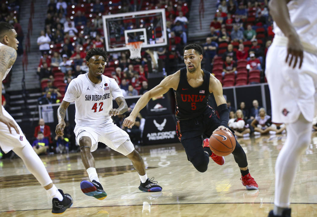 UNLV Rebels guard Noah Robotham (5) drives to the basket against San Diego State Aztecs guard Jeremy Hemsley (42) during the first half of a quarterfinal game in the Mountain West men's basketball ...