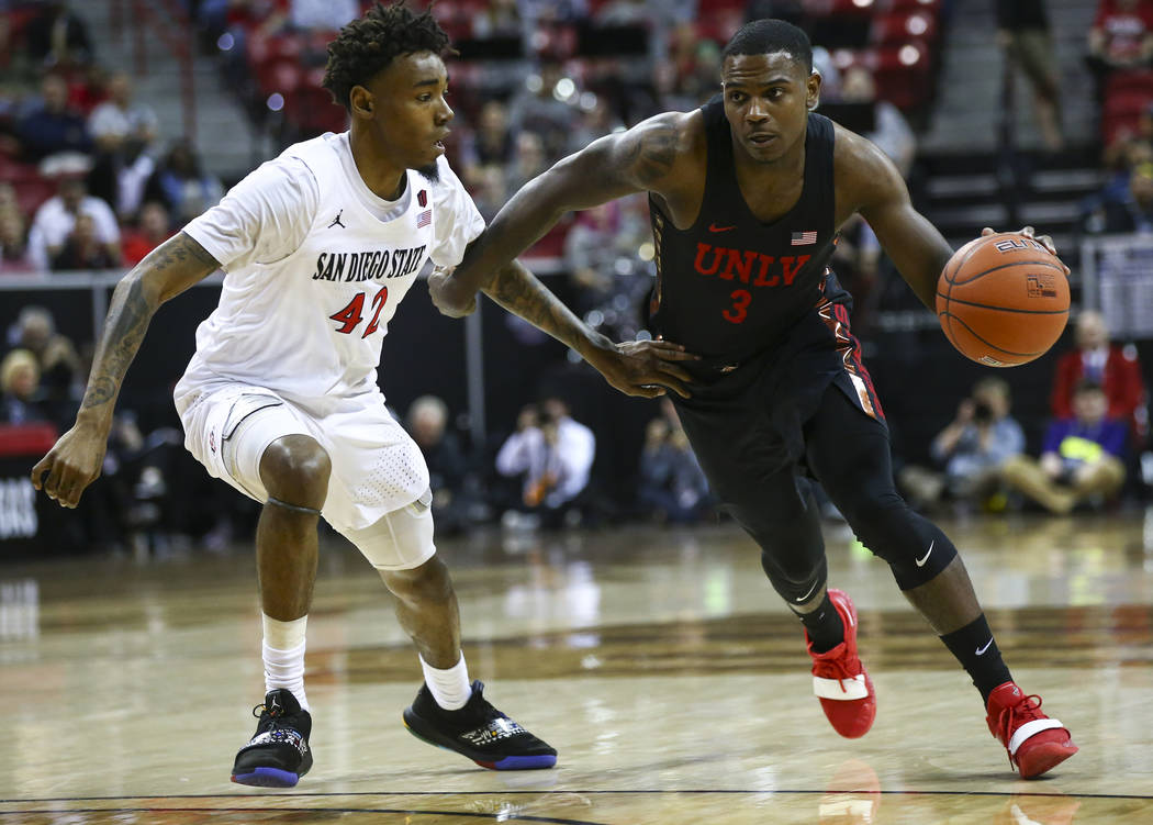 UNLV Rebels guard Amauri Hardy (3) brings the ball up court against San Diego State Aztecs guard Jeremy Hemsley (42) during the first half of a quarterfinal game in the Mountain West men's basketb ...
