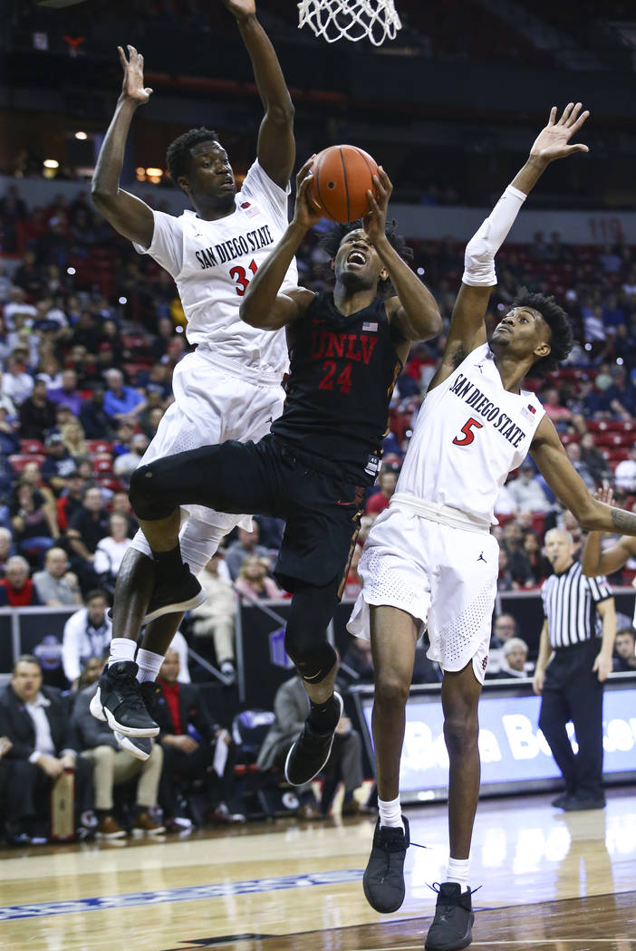 UNLV Rebels forward Joel Ntambwe (24) goes to the basket between San Diego State Aztecs forwards Nathan Mensah (31) and Jalen McDaniels (5) during the second half of a quarterfinal game in the Mou ...