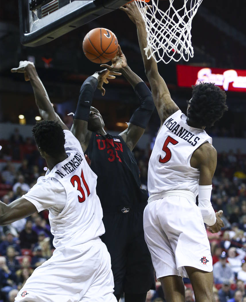 UNLV Rebels forward Cheikh Mbacke Diong (34) is fouled by San Diego State Aztecs forward Nathan Mensah (31) while going to the basket under pressure from San Diego State Aztecs forward Jalen McDan ...