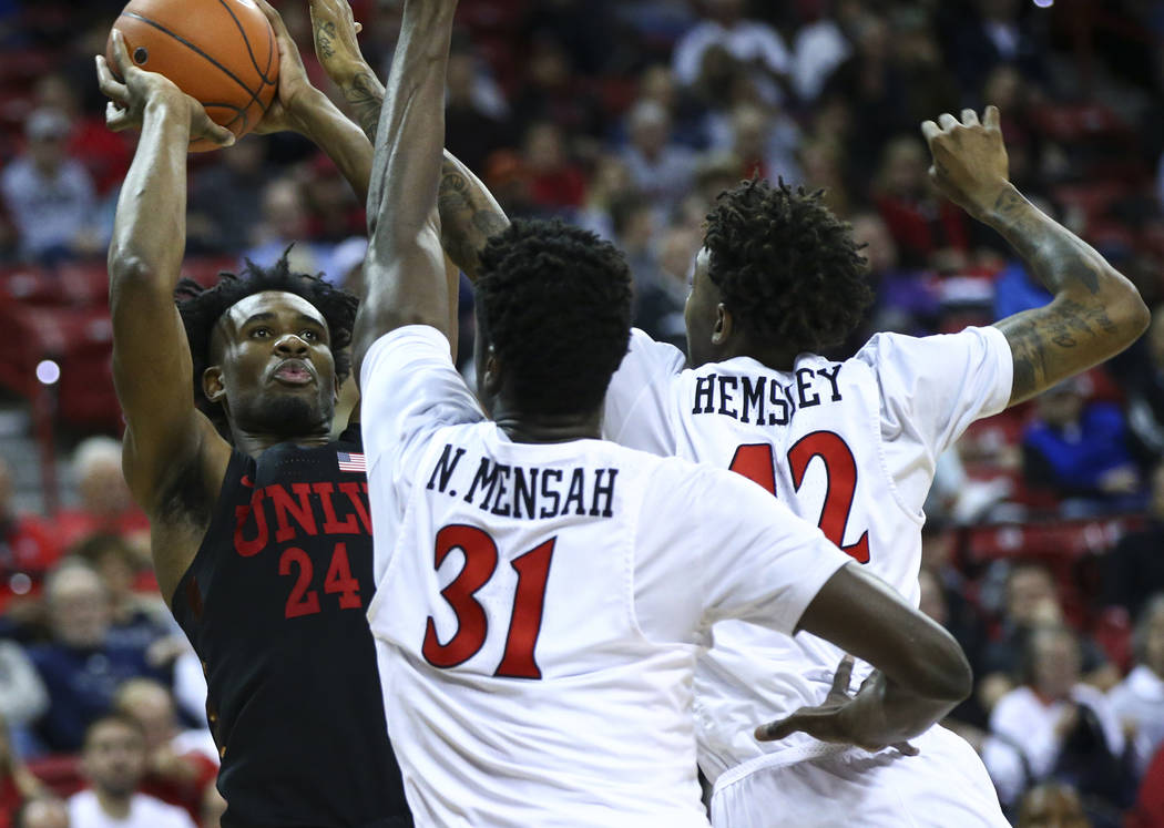 UNLV Rebels forward Joel Ntambwe (24) shoots under pressure from San Diego State Aztecs forward Nathan Mensah (31) and guard Jeremy Hemsley during the second half of a quarterfinal game in the Mou ...