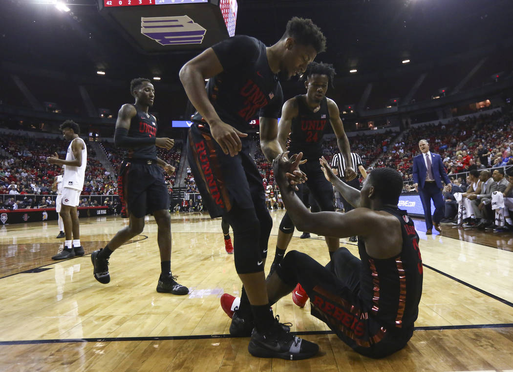 UNLV Rebels forwards Nick Blair (20) and Joel Ntambwe (24) help up guard Amauri Hardy (3) during the first half of a quarterfinal game against San Diego State in the Mountain West men's basketball ...