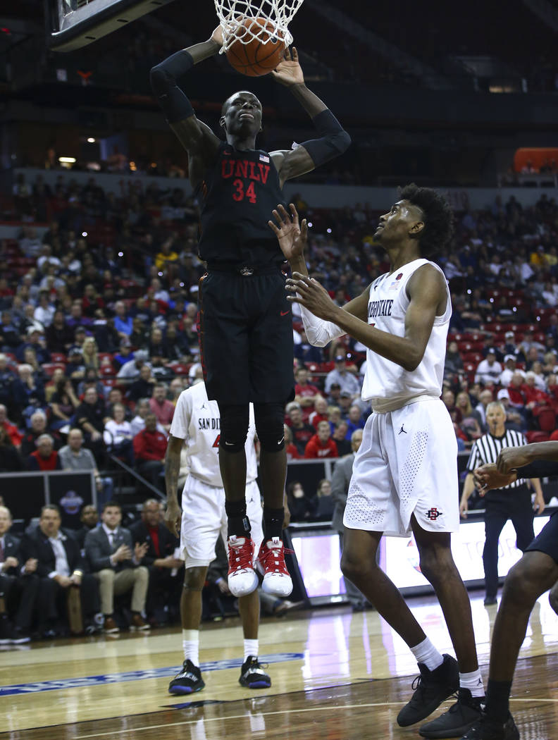 UNLV Rebels forward Cheikh Mbacke Diong (34) dunks over San Diego State Aztecs forward Jalen McDaniels during the second half of a quarterfinal game in the Mountain West men's basketball tournamen ...