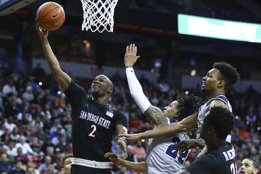 San Diego State Aztecs guard Adam Seiko (2) goes to the basket against UNR Wolf Pack guard Jazz Johnson (22) and forward Jordan Brown (21) during the first half of a semifinal basketball game in t ...