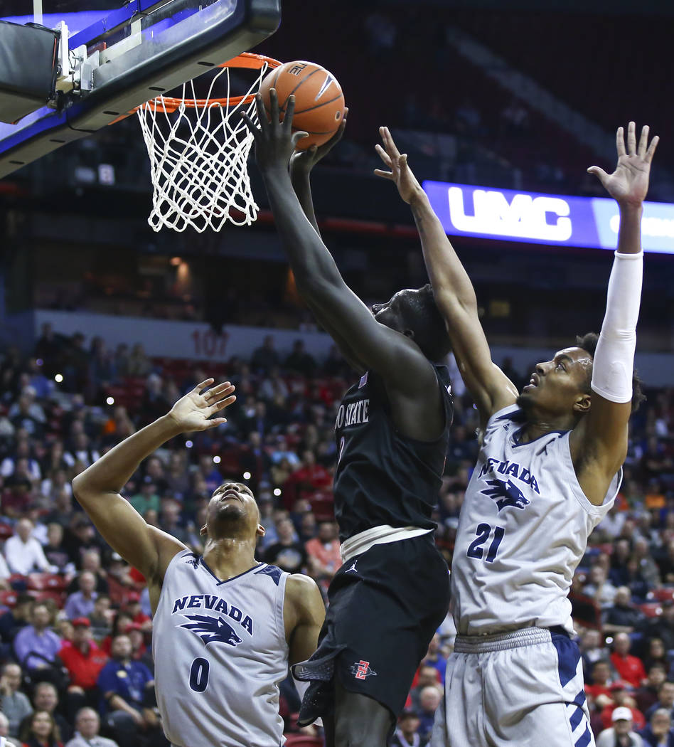 San Diego State Aztecs forward Aguek Arop (3) goes to the basket between UNR Wolf Pack forwards Tre'Shawn Thurman (0) and Jordan Brown (21) during the first half of a semifinal basketball game in ...