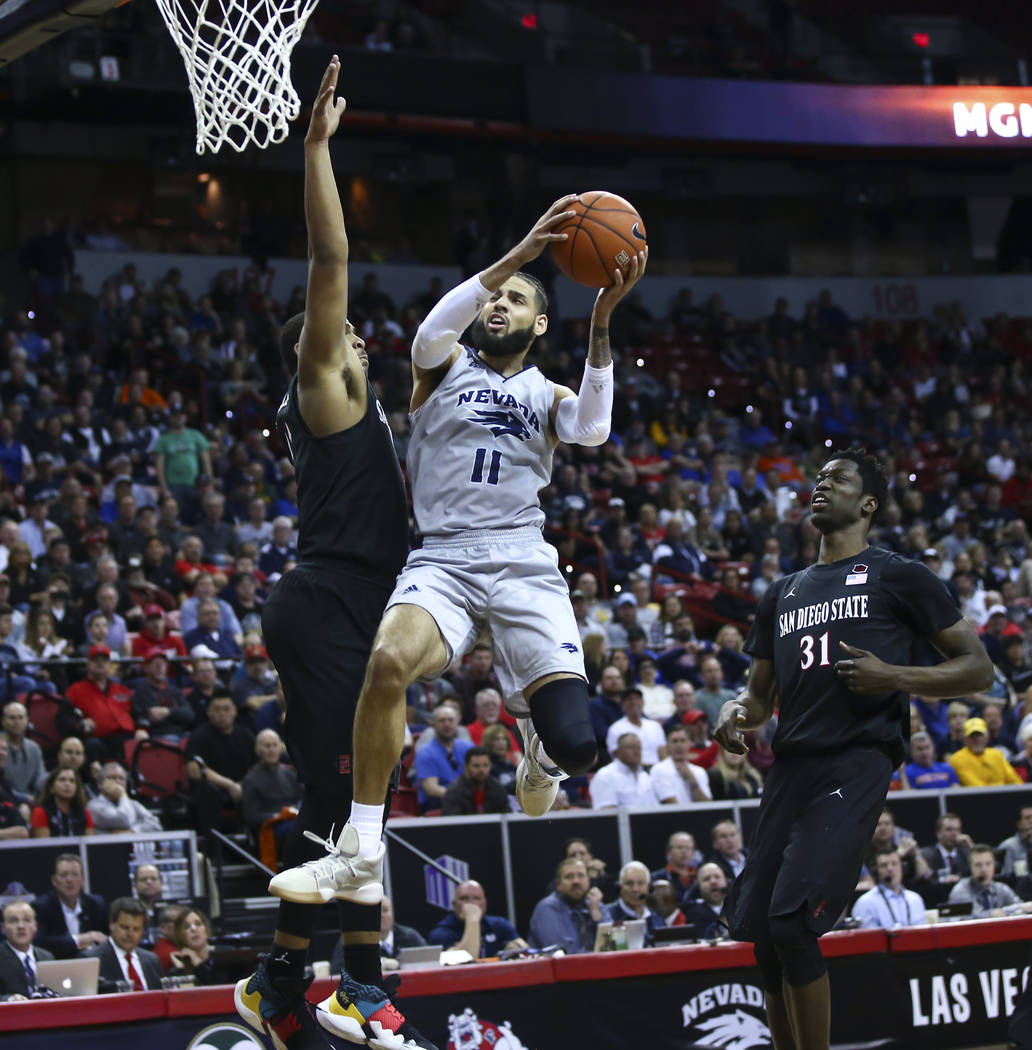 UNR Wolf Pack forward Cody Martin (11) goes to the basket between San Diego State Aztecs forwards Matt Mitchell and Nathan Mensah (31) looks on during the second half of a semifinal basketball gam ...