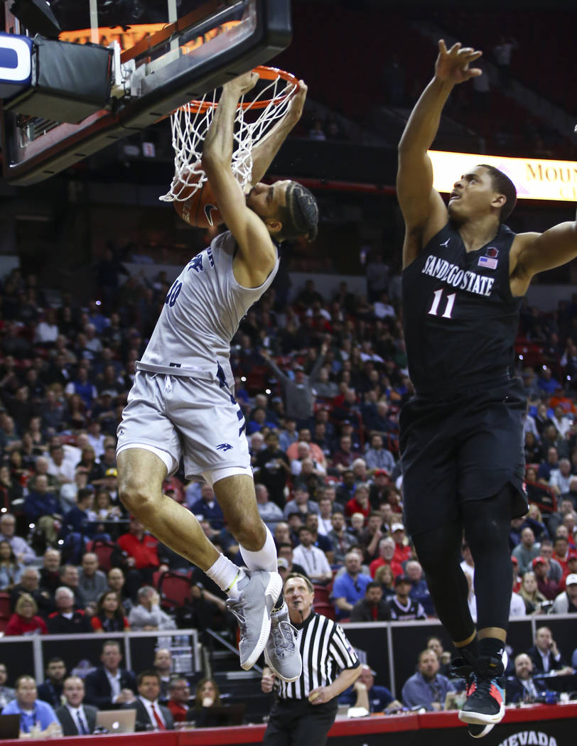 UNR Wolf Pack forward Caleb Martin (10) dunks in front of San Diego State Aztecs forward Matt Mitchell (11) during the second half of a semifinal basketball game in the Mountain West men's basketb ...