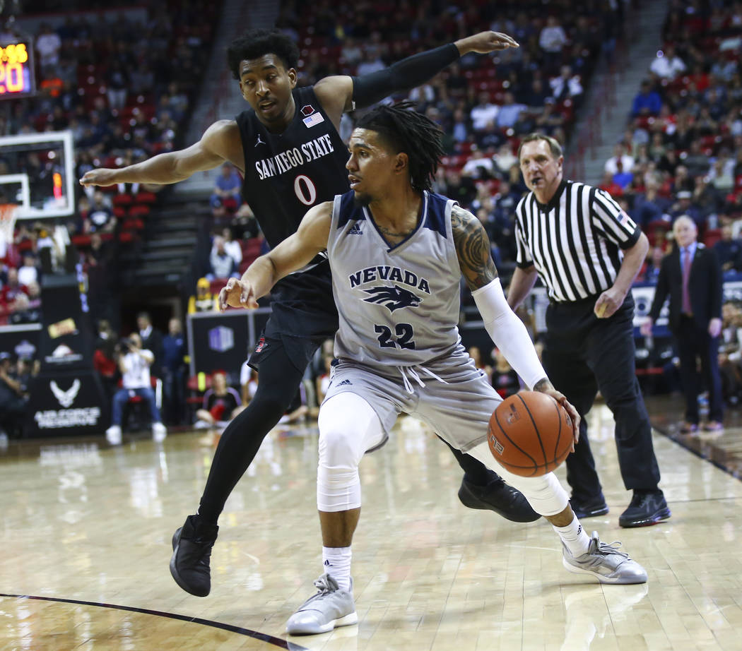 UNR Wolf Pack guard Jazz Johnson (22) moves the ball around under pressure from San Diego State Aztecs guard Devin Watson (0) during the second half of a semifinal basketball game in the Mountain ...