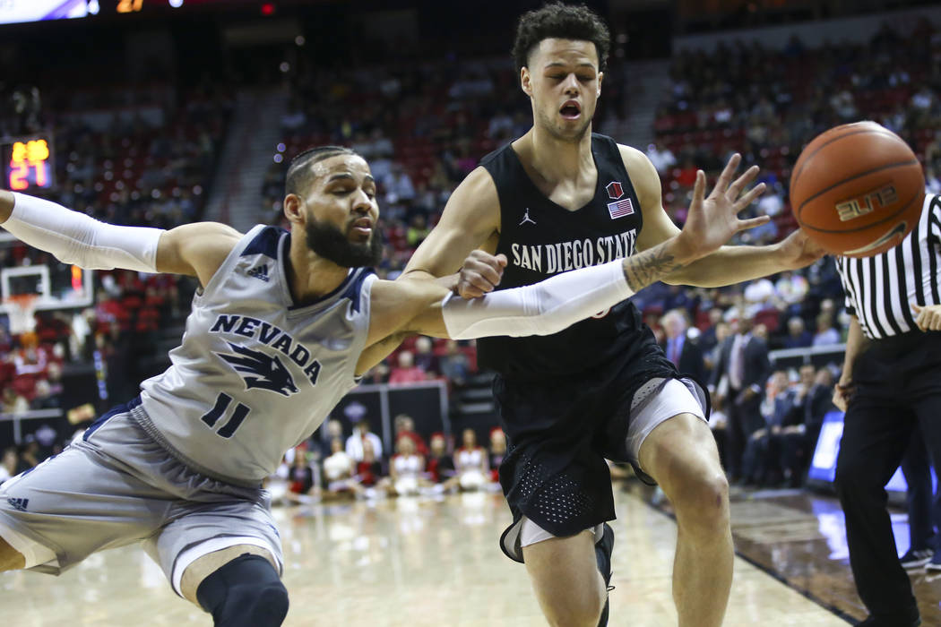 UNR Wolf Pack forward Cody Martin (11) and San Diego State Aztecs guard Jordan Schakel (20) battle for a loose ball during the first half of a semifinal basketball game in the Mountain West men's ...