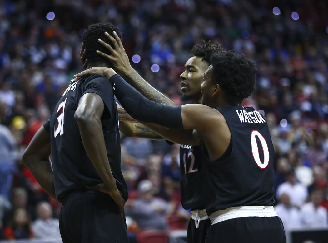 San Diego State Aztecs guards Jeremy Hemsley (42) and Devin Watson (0) console San Diego State Aztecs forward Nathan Mensah (31) after a foul was called on him during the second half of a semifina ...