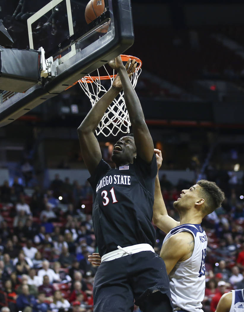 San Diego State Aztecs forward Nathan Mensah (31) goes to the basket against UNR Wolf Pack forward Trey Porter (15) during the first half of a semifinal basketball game in the Mountain West men's ...