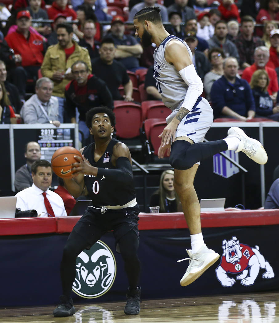 San Diego State Aztecs guard Devin Watson (0) waits to take a shot under pressure from UNR Wolf Pack forward Cody Martin (11) during the first half of a semifinal basketball game in the Mountain W ...