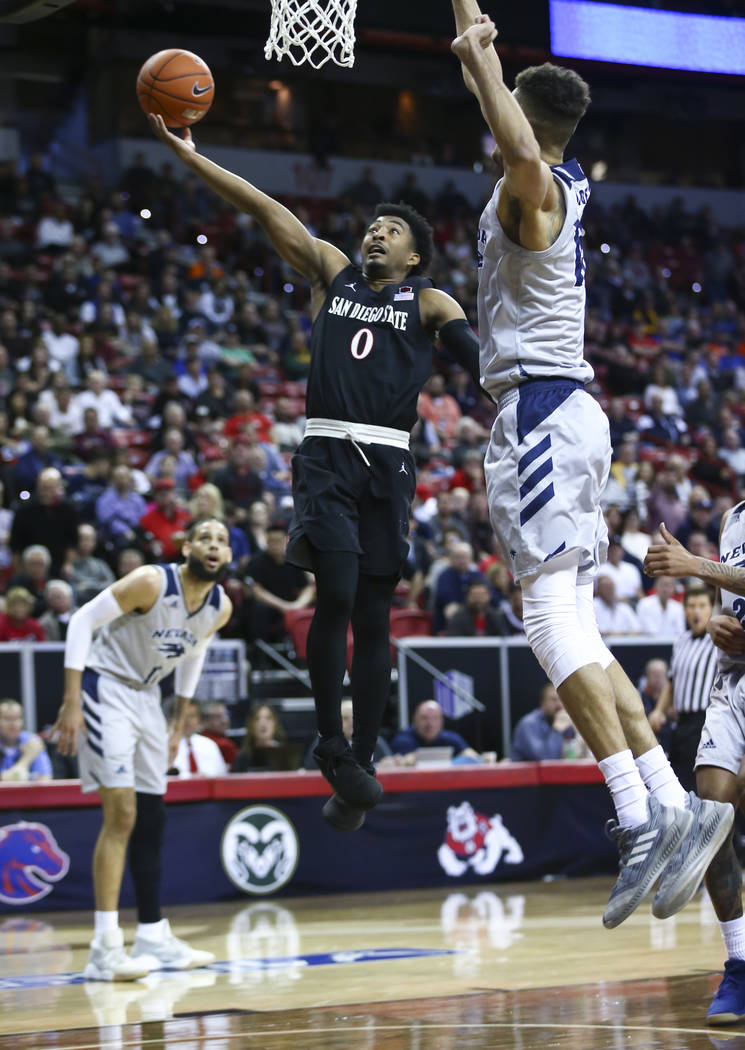 San Diego State Aztecs guard Devin Watson (0) goes to the basket against UNR Wolf Pack forward Trey Porter (15) during the first half of a semifinal basketball game in the Mountain West men's bask ...