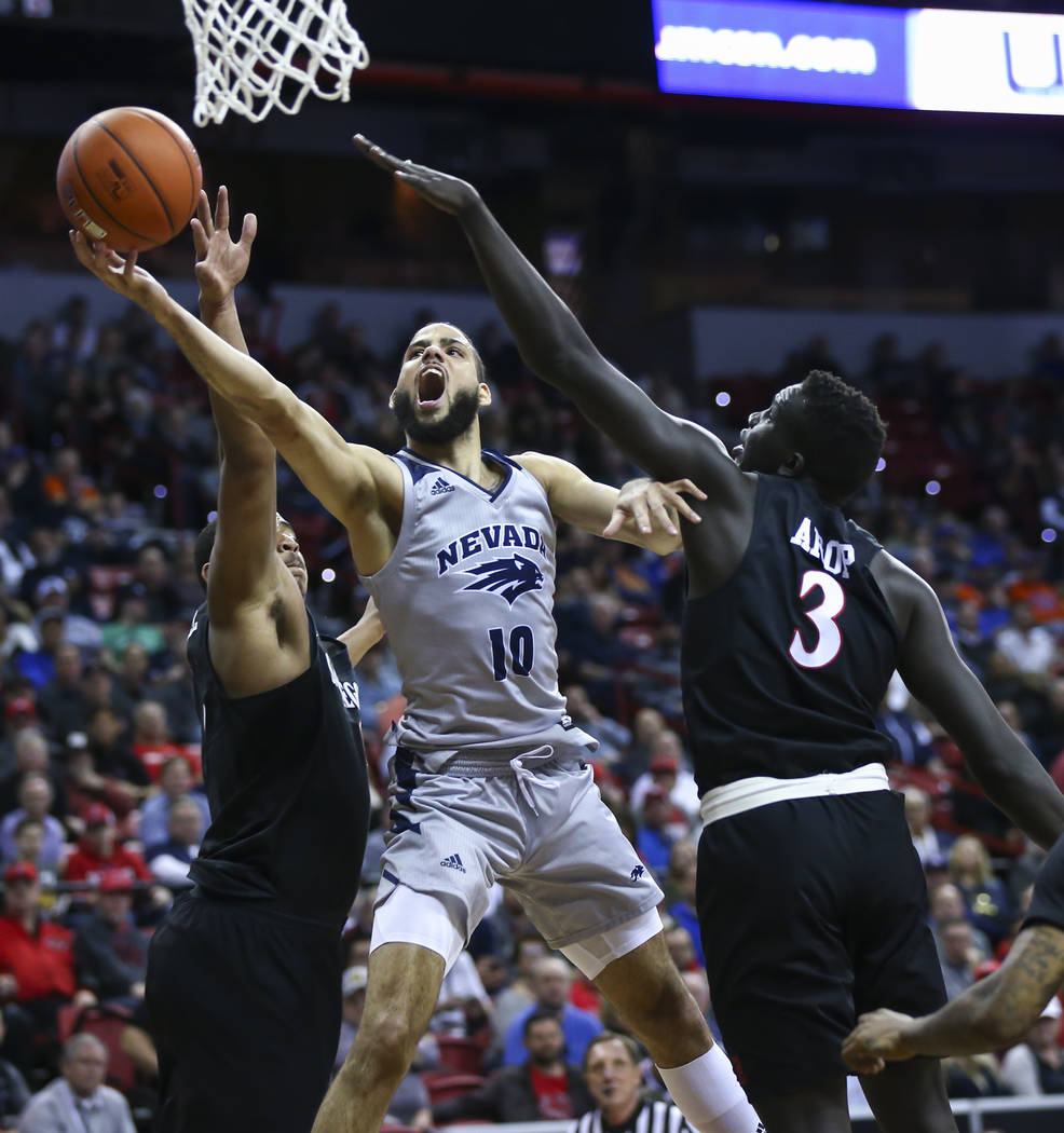 UNR Wolf Pack forward Caleb Martin (10) goes to the basket between San Diego State Aztecs forwards Matt Mitchell, left, and Aguek Arop (3) during the second half of a semifinal basketball game in ...
