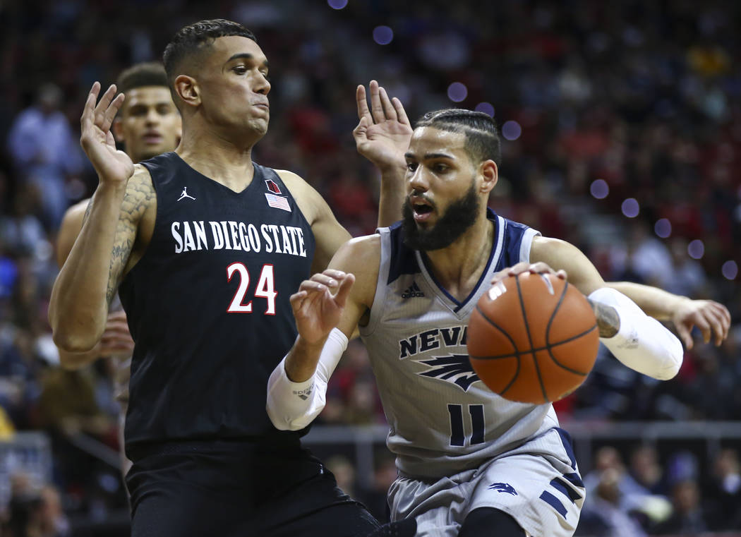 UNR Wolf Pack forward Cody Martin (11) drives against San Diego State Aztecs forward Nolan Narain (24) during the second half of a semifinal basketball game in the Mountain West men's basketball t ...