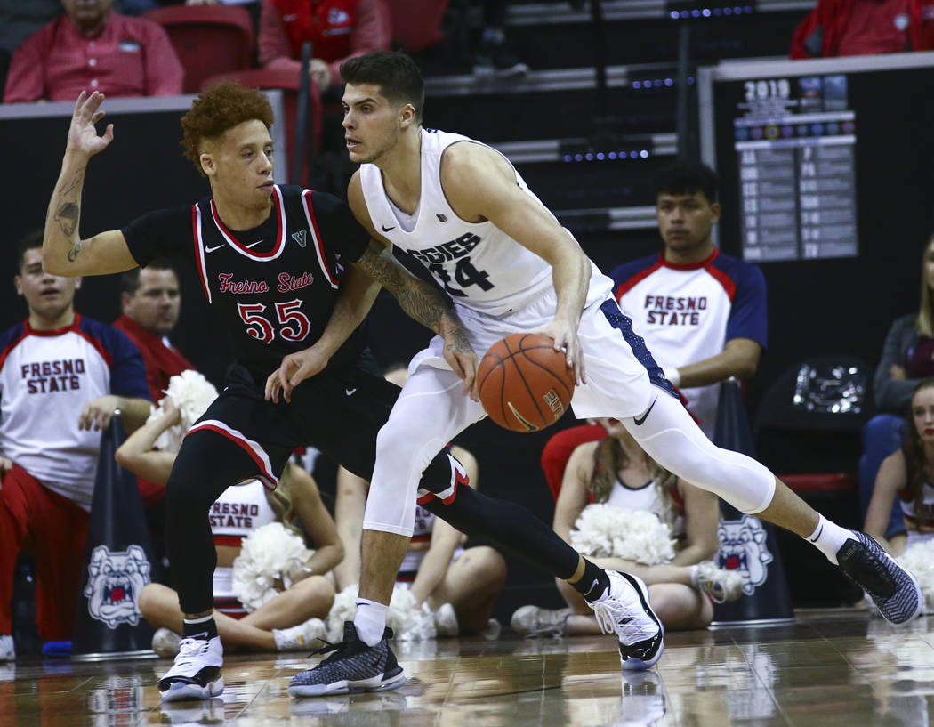 Utah State Aggies guard Diogo Brito (24) moves the ball around Fresno State Bulldogs guard Noah Blackwell (55) during the first half of a semifinal basketball game in the Mountain West men's baske ...