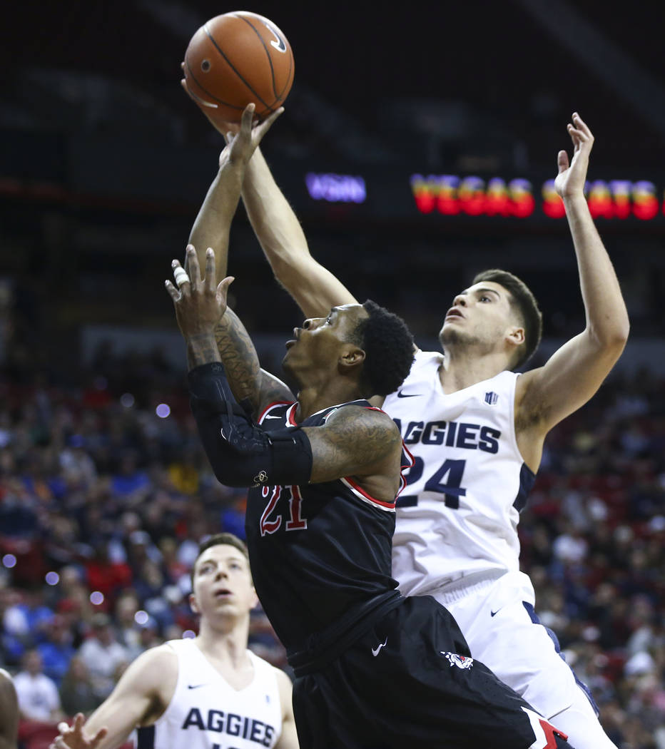 Fresno State Bulldogs guard Deshon Taylor (21) goes to the basket against Utah State Aggies guard Diogo Brito (24) during the first half of a semifinal basketball game in the Mountain West men's b ...