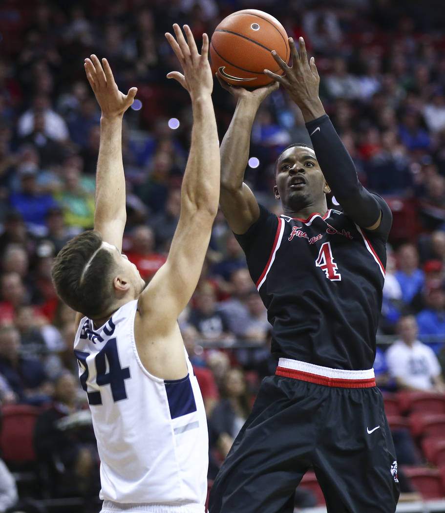 Fresno State Bulldogs guard Braxton Huggins (4) shoots over Utah State Aggies guard Diogo Brito (24) during the first half of a semifinal basketball game in the Mountain West men's basketball tour ...