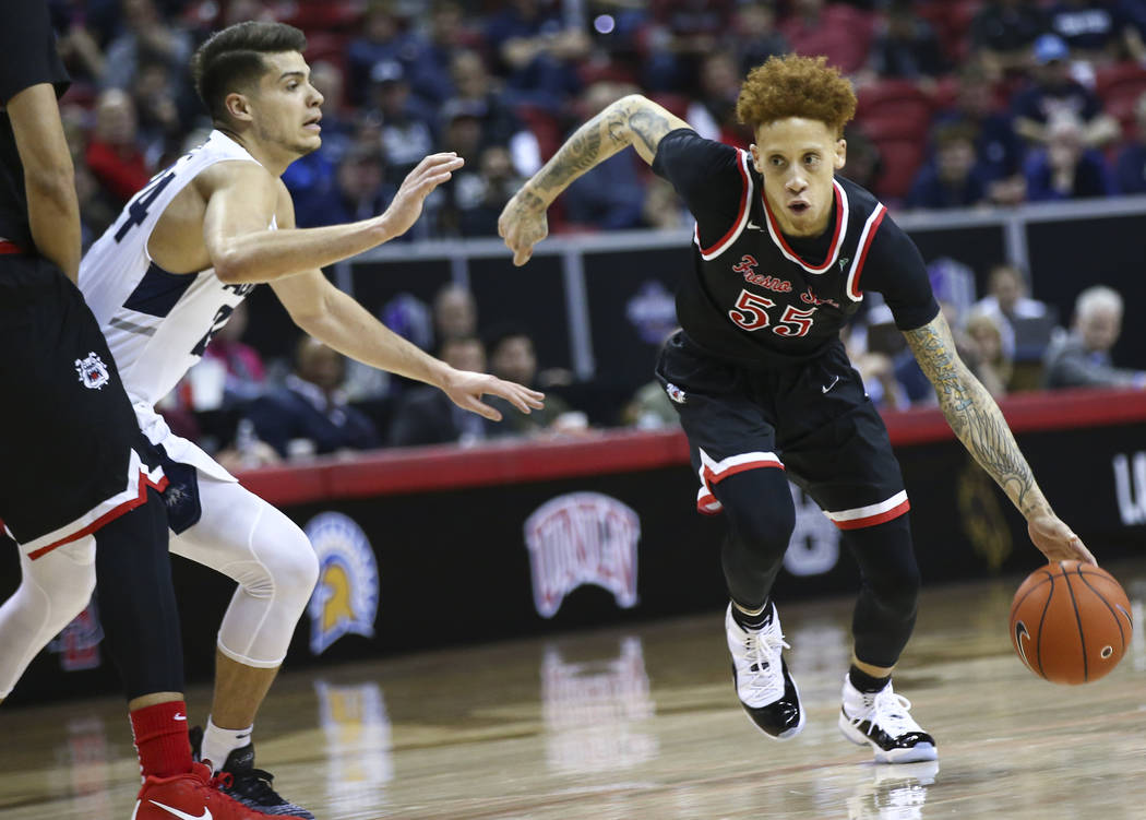 Fresno State Bulldogs guard Noah Blackwell (55) drives past Utah State Aggies guard Diogo Brito during the first half of a semifinal basketball game in the Mountain West men's basketball tournamen ...