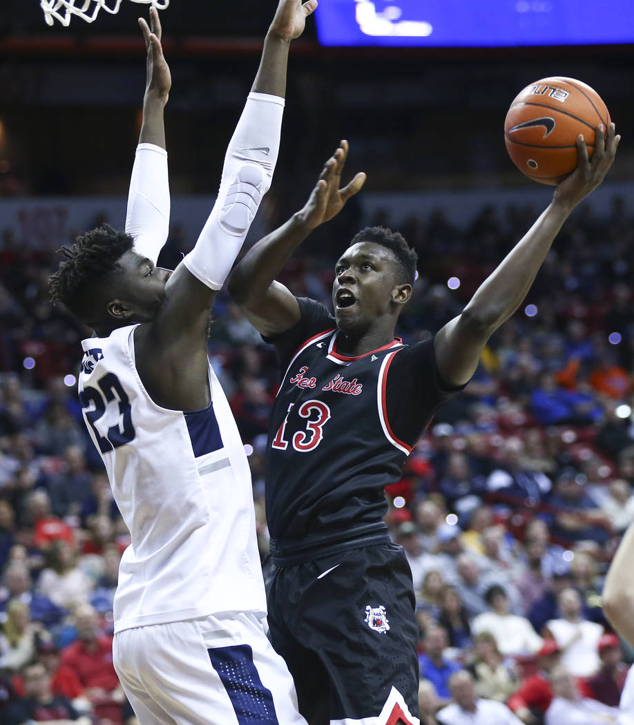 Fresno State Bulldogs guard Aguir Agau (13) goes to the basket againt Utah State Aggies center Neemias Queta (23) during the first half of a semifinal basketball game in the Mountain West men's ba ...