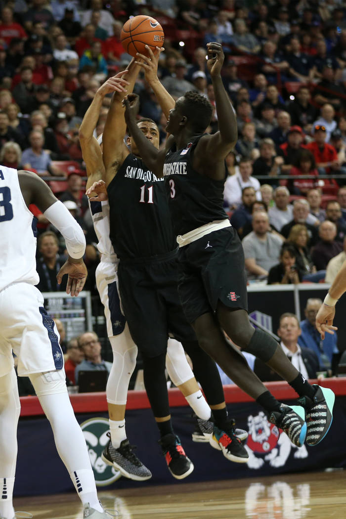 San Diego State Aztecs forward Matt Mitchell (11) leaps a loose ball with forward Aguek Arop (3) against Utah State Aggies in the first half of the Mountain West tournament men's basketball champi ...