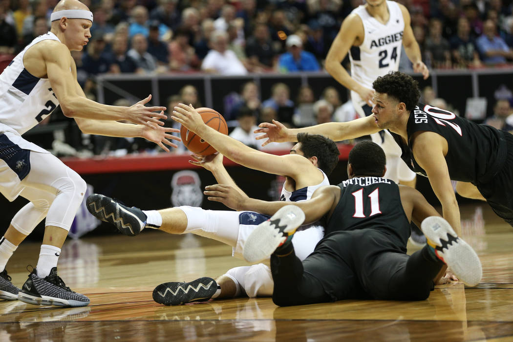 Utah State Aggies guard Abel Porter (15) makes a pass to guard Brock Miller (22) under pressure from San Diego State Aztecs forward Matt Mitchell (11) and guard Jordan Schakel (20) in the first ha ...