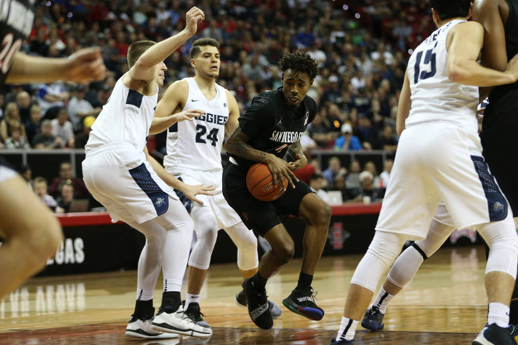 San Diego State Aztecs guard Jeremy Hemsley (42) drives the ball under pressure from Utah State Aggies forward Quinn Taylor (10) and guard Diogo Brito (24) in the first half of the Mountain West t ...
