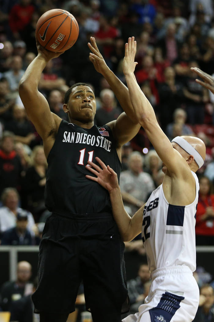 San Diego State Aztecs forward Matt Mitchell (11) shoots the ball under pressure from Utah State Aggies guard Brock Miller (22) in the first half of the Mountain West tournament men's basketball c ...
