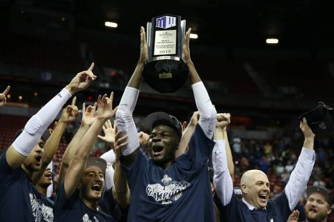 Utah State Aggies center Neemias Queta (23) raises the trophy after their win against San Diego State Aztecs in the Mountain West tournament men's basketball championship game at the Thomas & ...
