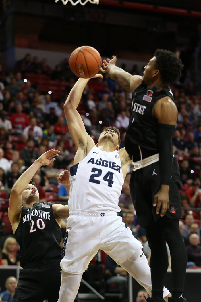 Utah State Aggies guard Diogo Brito (24) is fouled against San Diego State Aztecs guard Devin Watson (0) and guard Jordan Schakel (20) in the second half of the Mountain West tournament men's bask ...