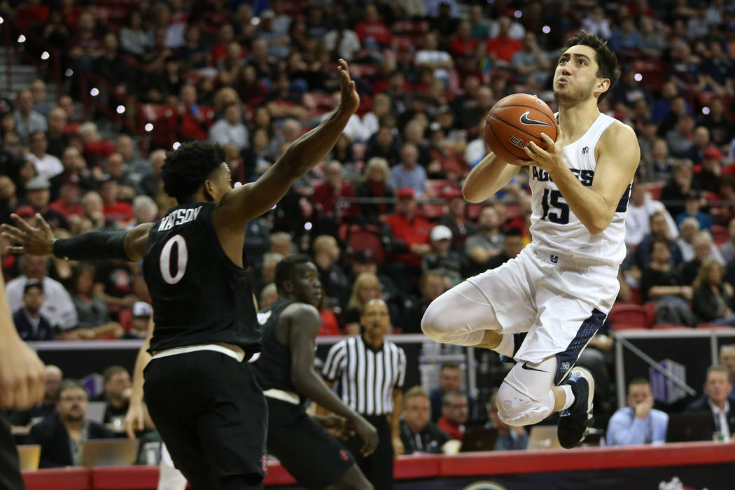 Utah State Aggies guard Abel Porter (15) goes up for a shot against San Diego State Aztecs guard Devin Watson (0) in the second half of the Mountain West tournament men's basketball championship g ...