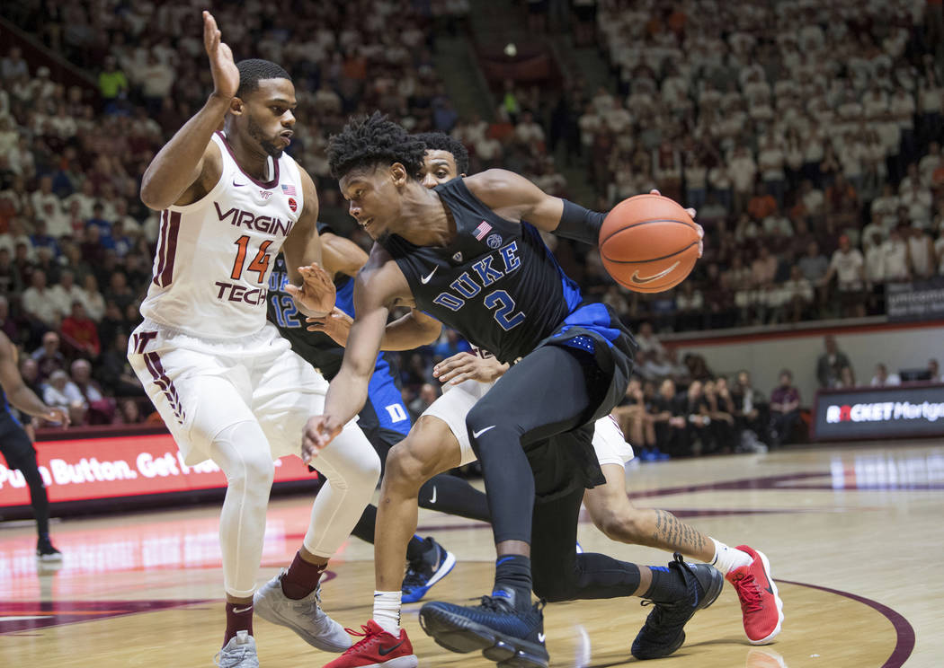 Duke foreword Cam Reddish (2) drives around Virginia Tech defender PJ Horne (14) during the first half of an NCAA college basketball game in Blacksburg, Va., Tuesday, Feb. 26, 2019. (AP Photo/Lee ...