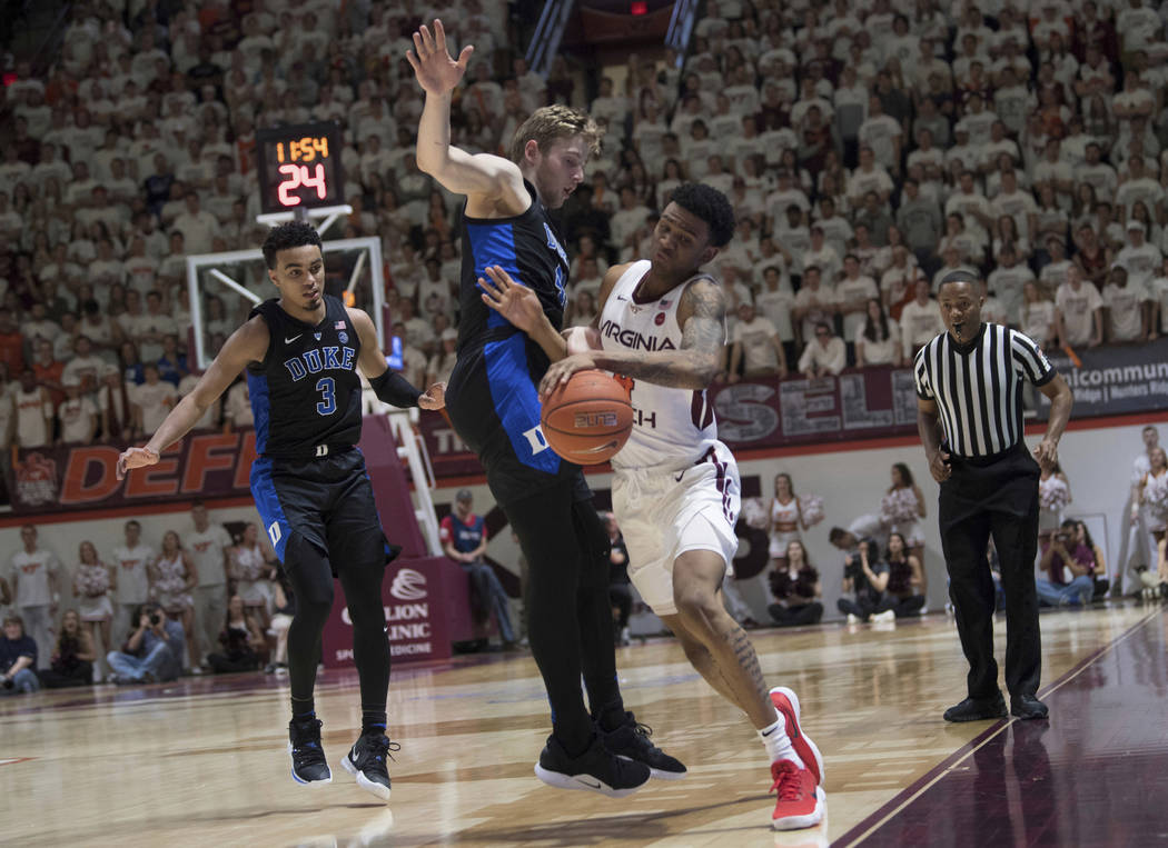 Virginia Tech guard Nickel Alexander-Walker, right, is fouled by Duke defender Jack White during the second half of an NCAA college basketball game in Blacksburg, Va., Tuesday, Feb. 26, 2019. (AP ...
