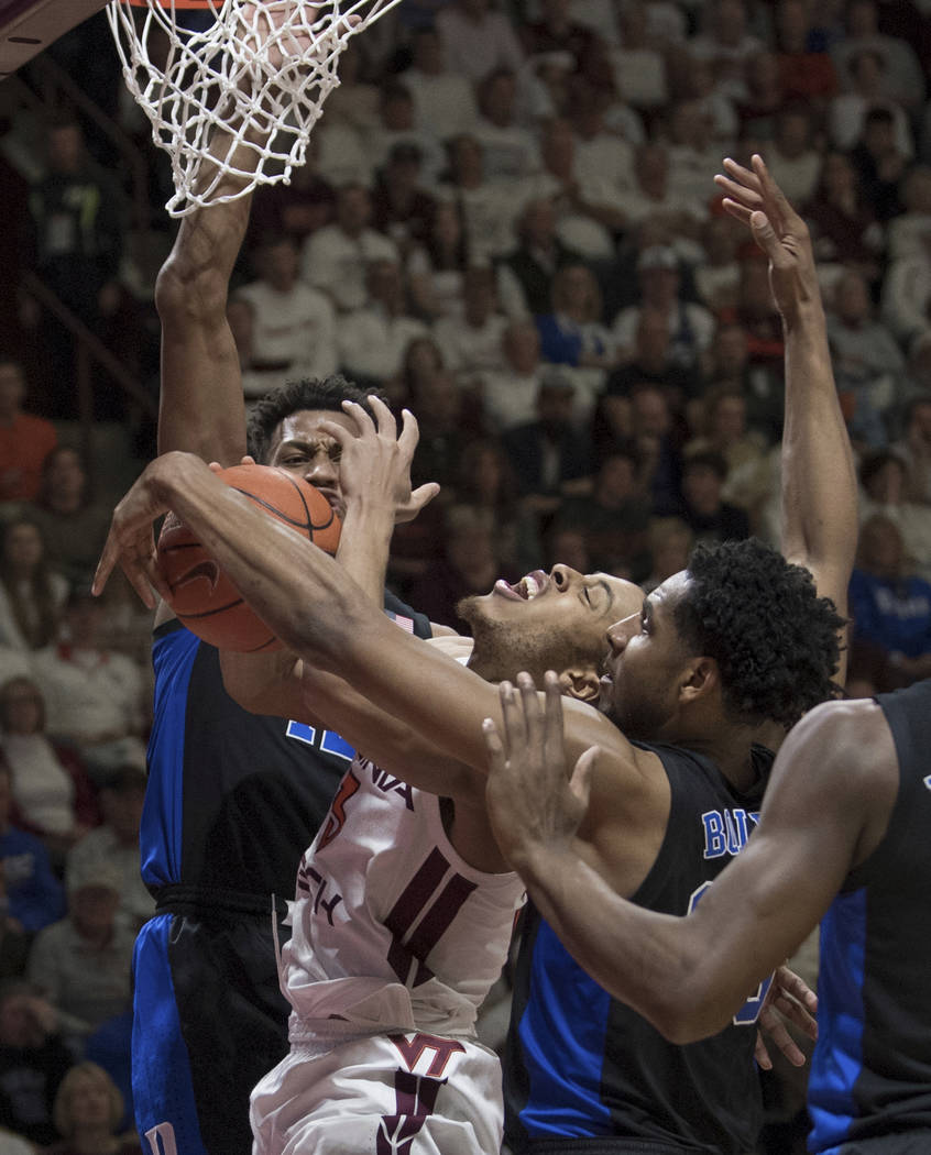 Virginia Tech guard Wabiss Bede (3) is fouled as Duke's Javin DeLaurier, top and Marquis Bolden defend during the second half of an NCAA college basketball game in Blacksburg, Va., Tuesday, Feb. 2 ...