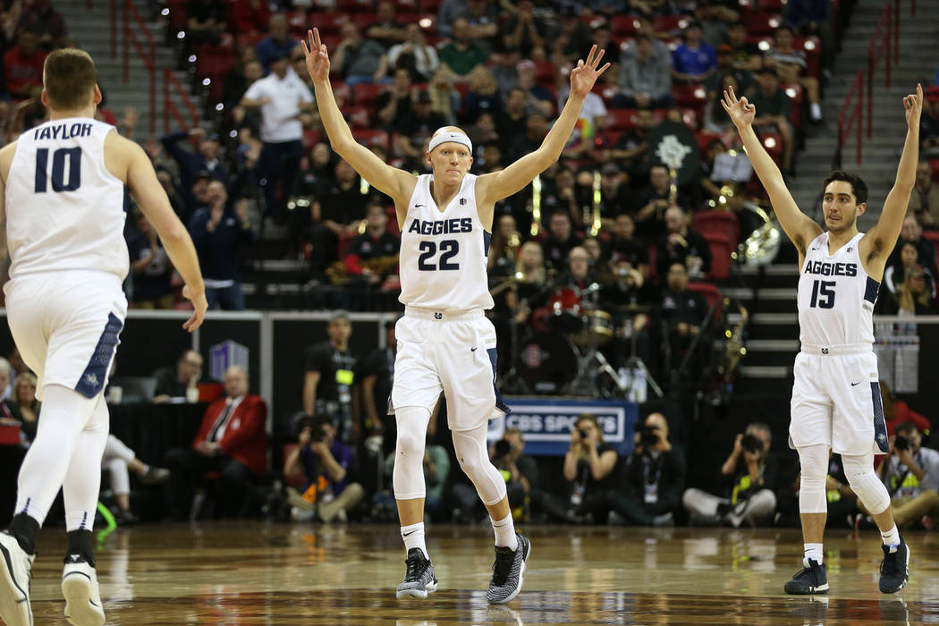 Utah State Aggies guard Brock Miller (22) with guard Abel Porter (15), reacts after making a three-point-shot against the San Diego State Aztecs in the second half of the Mountain West tournament ...