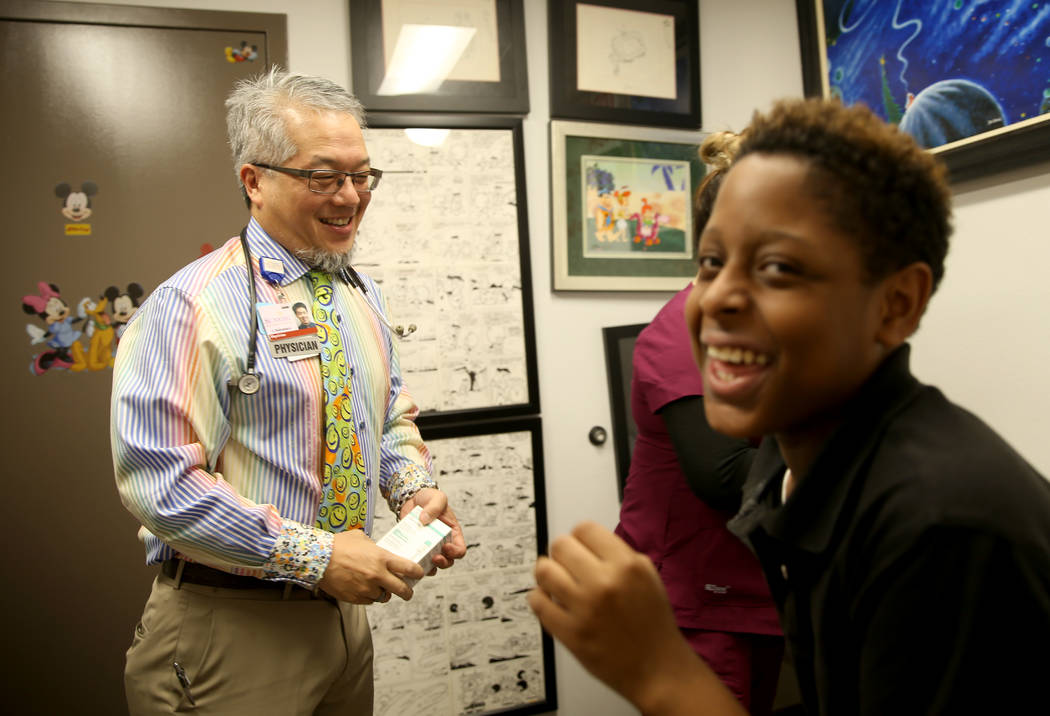 Pulmonologist Dr. Craig Nakamura, director of the Cystic Fibrosis Center of Southern Nevada, makes patient Aarin Shepard, 11, laugh before an examination at his Las Vegas office Thursday, March 7, ...