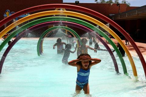 A girl runs under the cold water at Doolittle Community Center Pool. (File)
