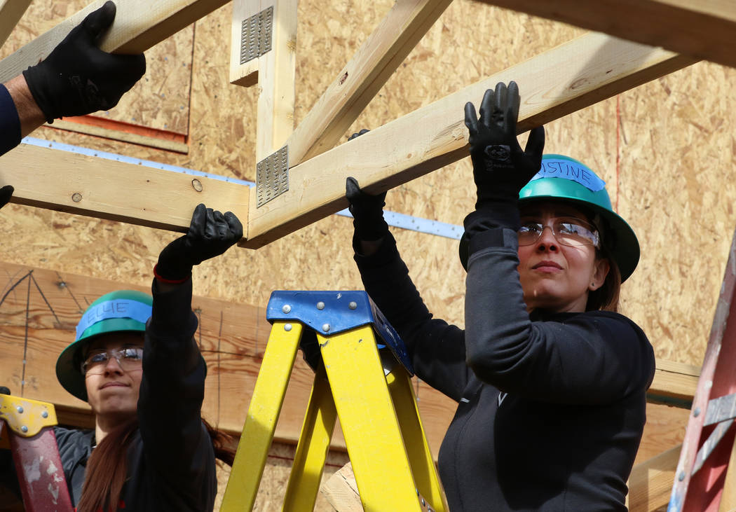 Ellie Lukova, left, and Christine Monjer of the Las Vegas Aces help raise roof trusses as they volunteer with the construction of Habitat for Humanity Las Vegas' 112th home in celebration of Int ...
