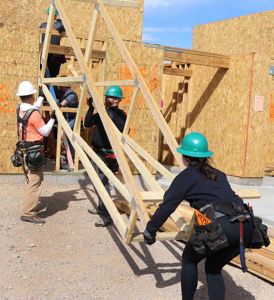 John Maxwell, left, site supervisor for Habitat for Humanity Las Vegas, Blake Broaddus, center, and Taylor Janison of the Las Vegas Aces help raise roof trusses as they volunteer with the construc ...