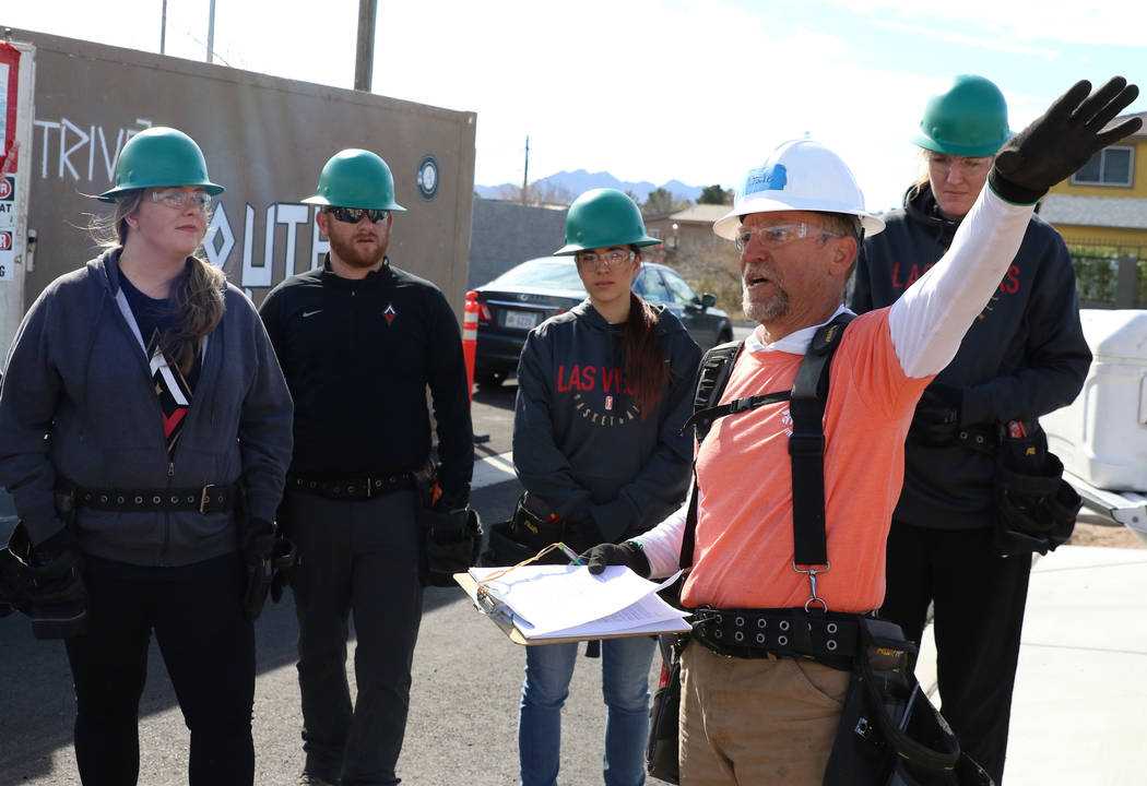 The Las Vegas Aces center Carolyn Swords, right, and members of the Las Vegas Aces front office staff listen as John Maxwell, site supervisor for Habitat for Humanity Las Vegas, talks about constr ...