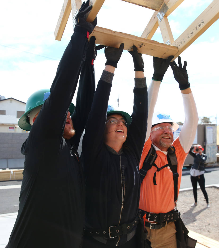 Blake Broaddus, left, Taylor Janison, center, of the Las Vegas Aces, and John Maxwell, right, site supervisor for Habitat for Humanity, raise roof trusses as they volunteer with the construction o ...