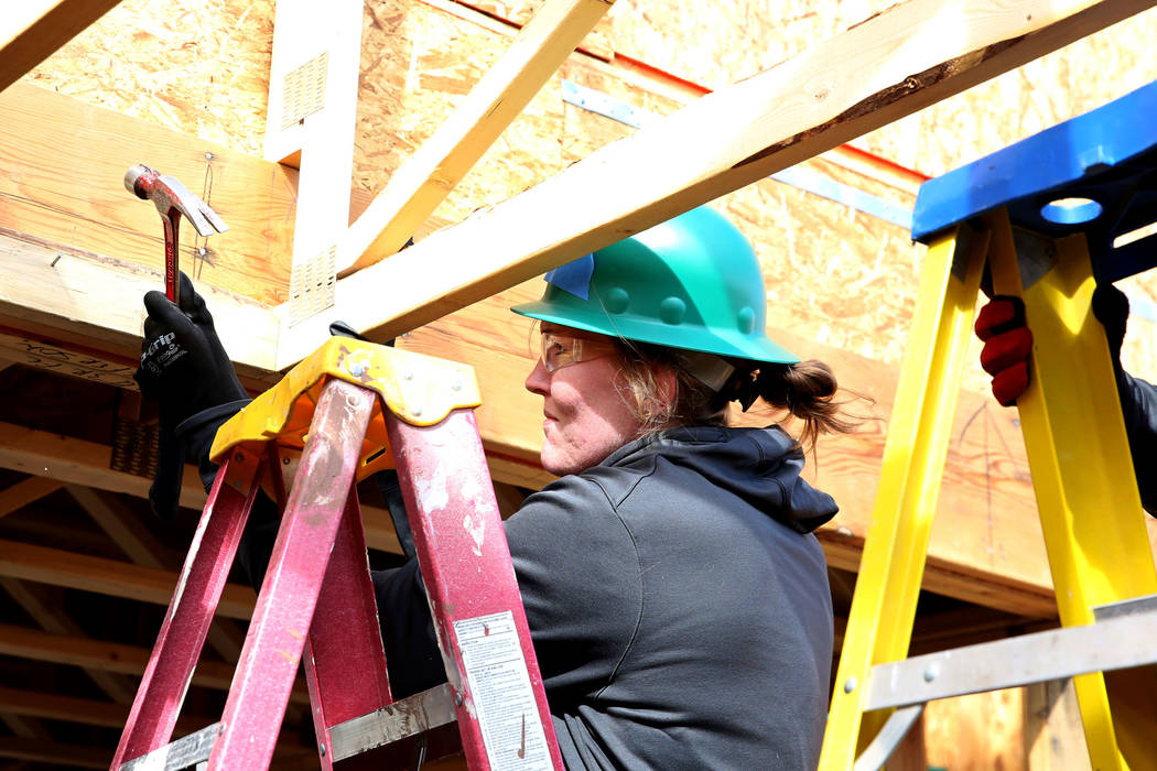 The Las Vegas Aces center Carolyn Swords hammers a nail as she volunteers with the construction of Habitat for Humanity Las Vegas' 112th home in celebration of International Women's Day on Friday, ...
