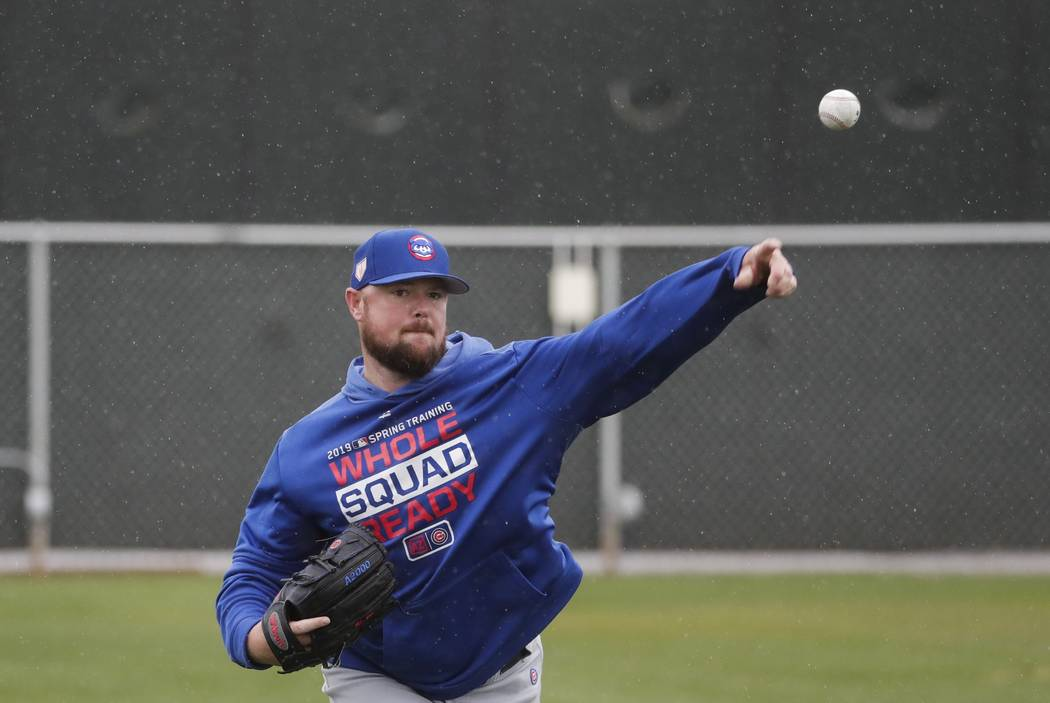 Chicago Cubs' Jon Lester throws in the rain during a spring training baseball workout Monday, Feb. 18, 2019, in Mesa, Ariz. (AP Photo/Morry Gash)
