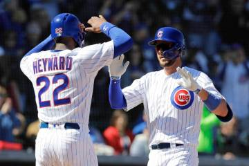 Chicago Cubs' Kris Bryant, right, celebrates with Jason Heyward after hitting a two-run home run during the first inning of a spring training baseball game against the Milwaukee Brewers, Saturday, ...