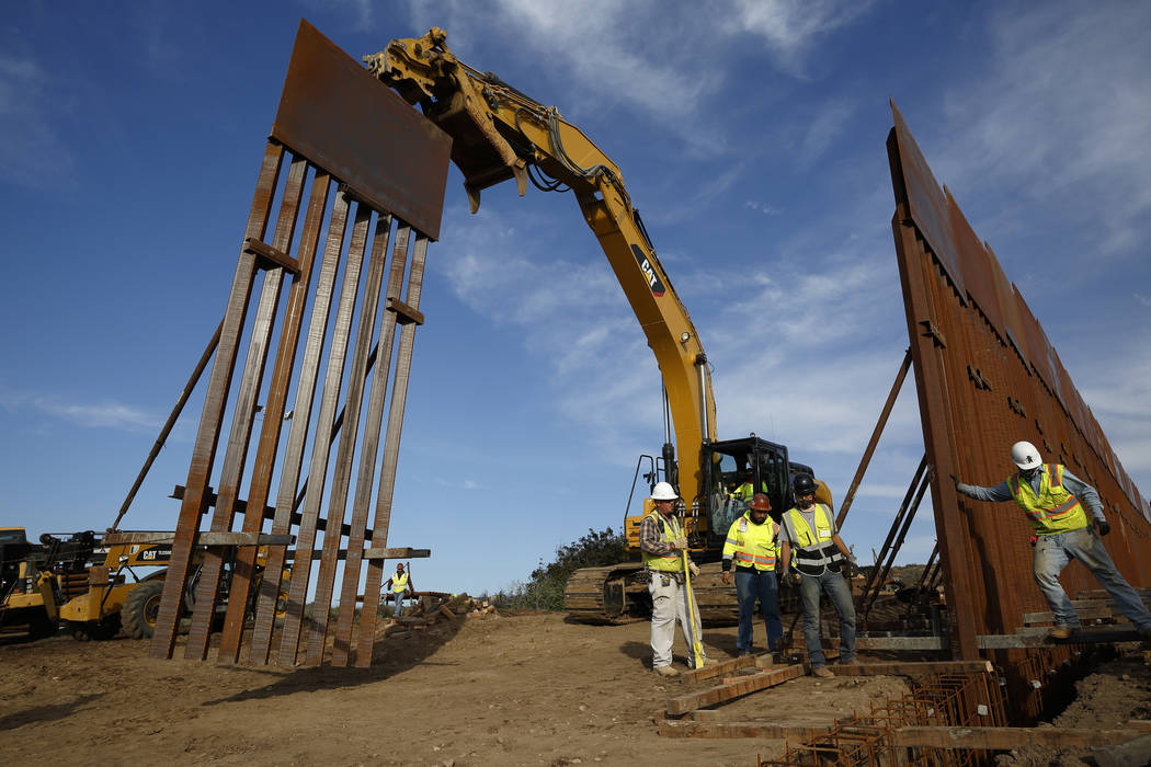 In this Jan. 9, 2019 file photo, construction crews install new border wall sections seen from Tijuana, Mexico. (AP Photo/Gregory Bull, File)