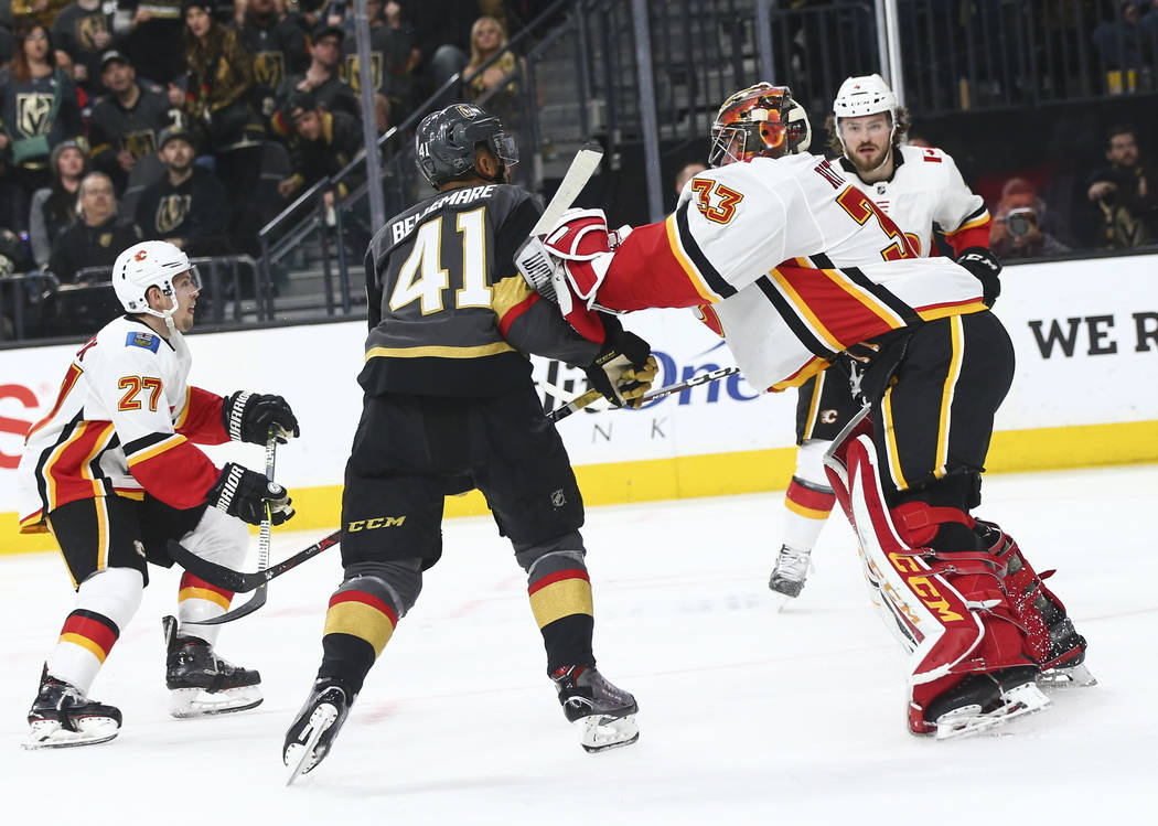 Calgary Flames goaltender David Rittich (33) pushes Golden Knights center Pierre-Edouard Bellemare (41) during the second period of an NHL hockey game at T-Mobile Arena in Las Vegas on Wednesday, ...