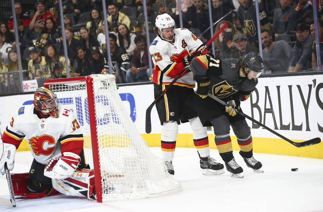 Golden Knights center William Karlsson (71) moves the puck under pressure from Calgary Flames center Sean Monahan (23) as goaltender David Rittich (33) looks on during the second period of an NHL ...