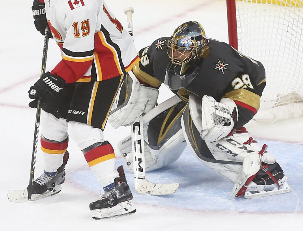 Golden Knights goaltender Marc-Andre Fleury (29) defends the net in front of Calgary Flames left wing Matthew Tkachuk (19) during the third period of an NHL hockey game at T-Mobile Arena in Las Ve ...